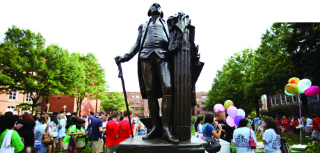Students mingle around the statue of George Washington on the Quad