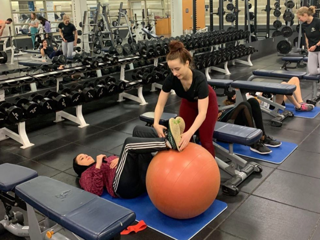 Fitness instructor assisting a student with their workout